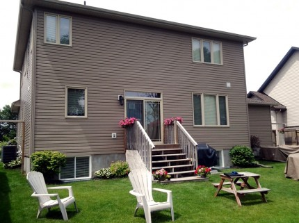 ottawa home with steps leading to backyard with green grass and chairs before custom deck build