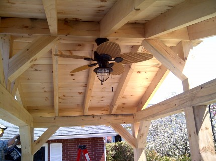 looking up at fan installed in the ceiling of custom wood pergola
