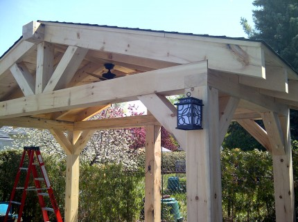outer view of custom wooden pergola with lantern hanging on front post