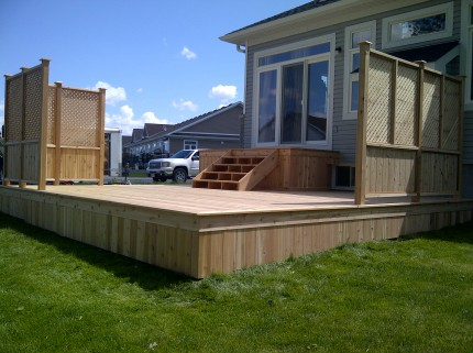 custom wooden deck with two corner fences and a platform with stairs from the house