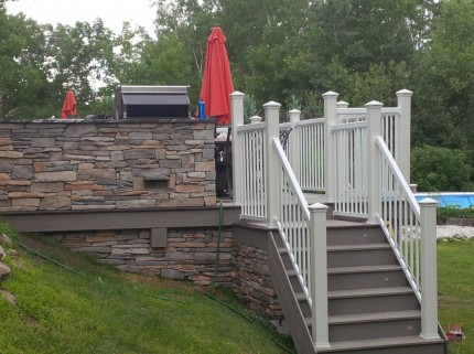 custom deck with stone walls and stairs with railings leading to backyard grass