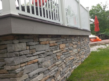 low angle view of custom deck with stone wall foundation