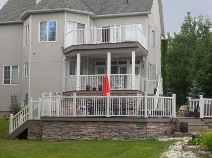 view of large grey two storey home that has a custom deck with railings and a stone wall pattern foundation