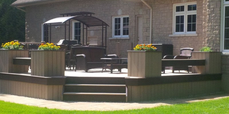 low height custom deck attached to modern home in Ottawa with planters around the perimeter
