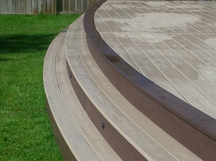 custom deck steps leading down to green grass of backyard