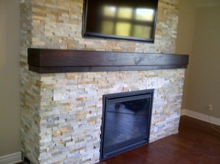 interior fireplace with brick pattern enclosure wooden shelf and mounted flat screen tv