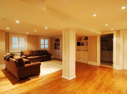 newly renovated basement in ottawa with hardwood floors shelving and couches