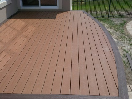 pristine newly constructed custom deck with curved edge facing backyard
