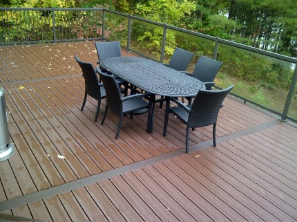 wet custom deck with railings and a patio tableset and chairs in the middle