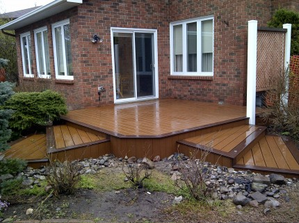wet small custom deck with two sets of stairs leading in different directions from back door of house
