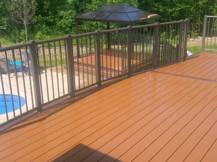 pristine custom deck with railings and a pergola in the background