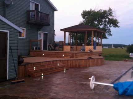 custom multi-level deck with pergola and lights embedded in the steps