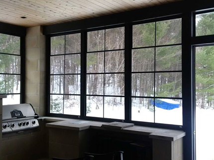 enclosed porch with barbecue looking out into wintery forest