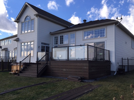 dark custom deck attached to two storey home with glass railings
