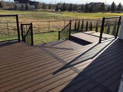 clean custom deck with black railings overlooking backyard and field