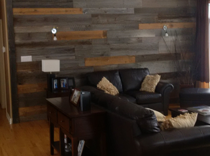 living room with black couches and wall with pattern of wooden planks