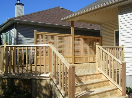 Wooden custom deck attached to bungalow with stairs leading to backyard