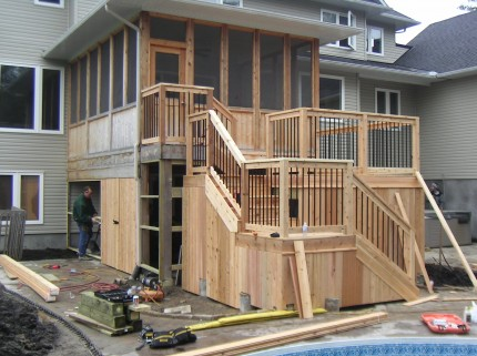 under construction two level wooden deck attached to sunroom