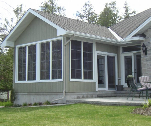 bungalow with large windows and concrete patio with furniture