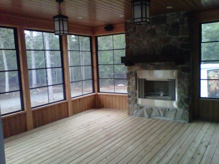 Screened in wooden porch with fireplace